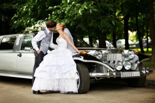 Happy groom adn bride about retro limousine